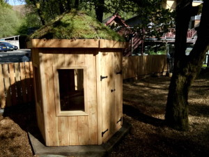 Children's den at The Centre for Alternative Energy sitting in the dappled shade of their adventure play area.